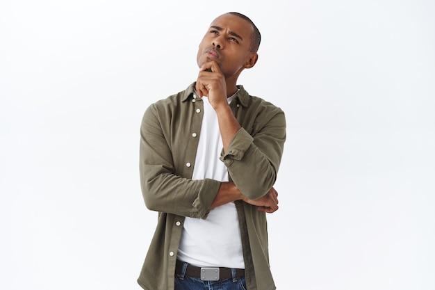 Hmm interessant. porträt eines nachdenklichen, gutaussehenden, intelligenten afroamerikanischen mannes, der denkt und die wahl trifft