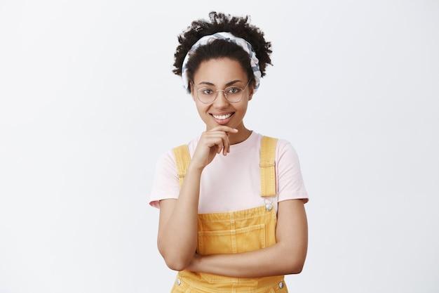 Hmm tolles konzept, lass es uns machen. erfreut attraktive junge afroamerikanische internet-bloggerin in brille, stirnband und gelben overalls, lächelnd und händchen haltend am kinn, plan annehmen