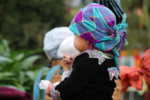 Hmong-mädchen kleidete in der hand im bunten handgewebten stoff an, der lebensmittel hält