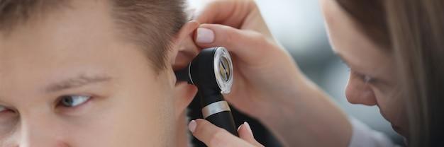 Hno-arzt untersucht ohr eines kranken mannes mit otoskop-nahaufnahme