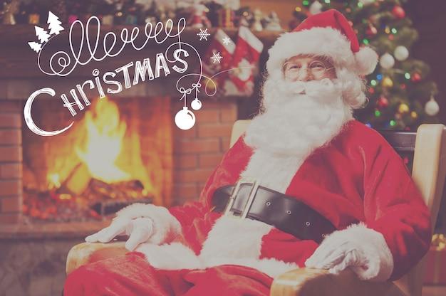 Ho ho ho! traditioneller weihnachtsmann sitzt an seinem stuhl und lächelt mit kamin und weihnachtsbaum im hintergrund