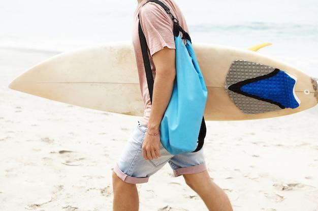 Hobby, aktiver lebensstil und sommerferienkonzept. beschnittener schuss des jungen touristen mit tasche, die entlang sandstrand geht