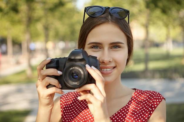 Hobby-, freizeit-, berufs- und sommerkonzept. entzückende glückliche junge studentin, die fotos von menschen und natur im park mit dslr-kamera macht, lächelnd, freudigen gesichtsausdruck habend