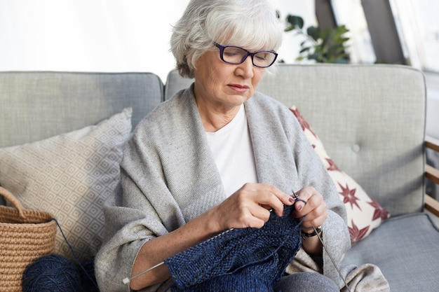 Hobby-, freizeit- und ruhestandskonzept. gut aussehende elegante großmutter mit brille, die auf einer grauen couch mit nadeln sitzt, einen pullover für ihren enkel strickt und einen ernsthaften, konzentrierten blick hat