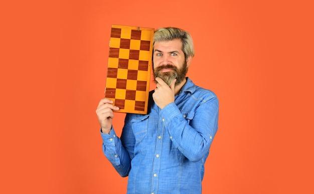 Hobby und freizeit. intellektuelle spiele. schachunterricht. schachwettbewerb für lehrer. schachfiguren. konzept der spielstrategie. brettspiel. mann, der schach spielt. intelligenter bärtiger hipster. kognitive fähigkeiten.