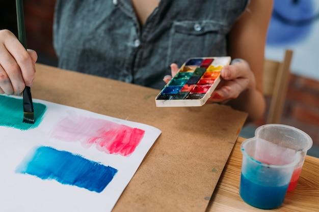 Hobby und kreativität. beschnittener schuss der jungen künstlerin, die abstrakte kunstwerke mit aquarell malt.