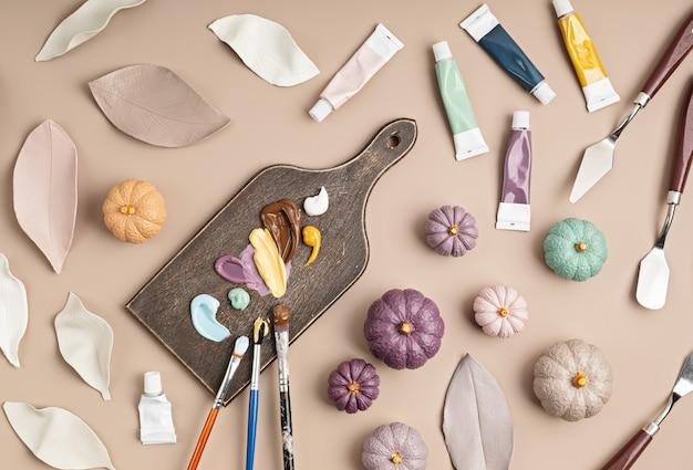 Hobbyhintergrund mit handgemachten tonblättern und kürbissen, pinseln und kunstzubehördiy, basteldekoration für herbstferienflache lage, draufsicht