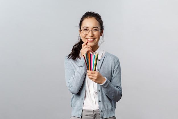 Hobbys, kreativität und kunstkonzept. dumme glücklich lächelnde asiatische frau, künstlerin in brille kichert als mit buntstiften, hat interessante idee für ihr nächstes kunstwerk, zeichnungsbild, grauer hintergrund.