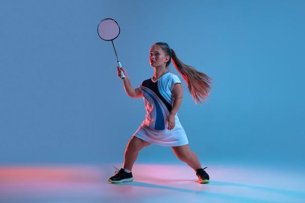 Hoch oben. schöne zwergfrau, die im badminton übt, lokalisiert auf blauem hintergrund im neonlicht. lebensstil inklusiver menschen, vielfalt und gleichberechtigung. sport, aktivität und bewegung. exemplar.