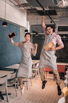 Hoch springen. stilvolles glückliches paar, das hoch springt, während es sich erstaunlich fühlt, familienunternehmen zu eröffnen