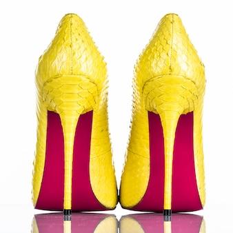 Hochabsatzschuh der modischen frau lokalisiert auf weißem hintergrund. schöner gelber weiblicher high heels schuh. luxus. rückansicht