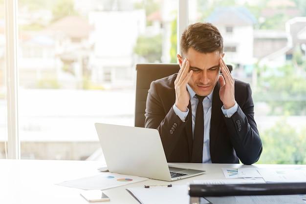 Hochdruck des geschäftsmannes im büro. ernsthaft arbeiten, kopfschmerzen.