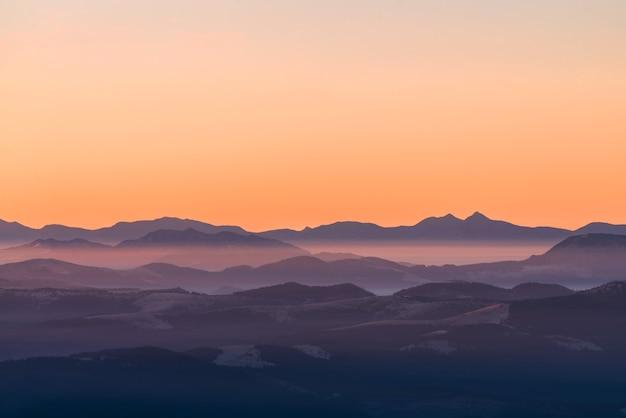 Hochgebirge im dichten nebel. schichten von bergen im dunst während des sonnenuntergangs. mehrschichtige neblige berge.