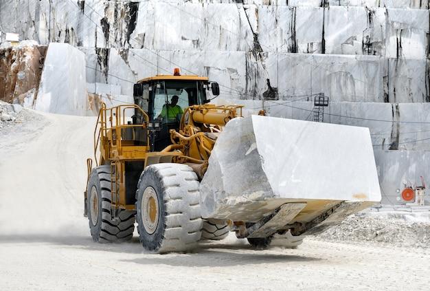 Hochleistungs-frontlader, der einen großen block aus weißem carrara-marmor in einer tagebaugrube oder einem steinbruch in der toskana, italien, bewegt