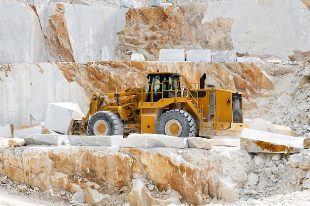 Hochleistungs-frontlader, der marmor in einem steinbruch oder einer mine in carrara, toskana, italien, während der gewinnung des felsens von einem berg transportiert