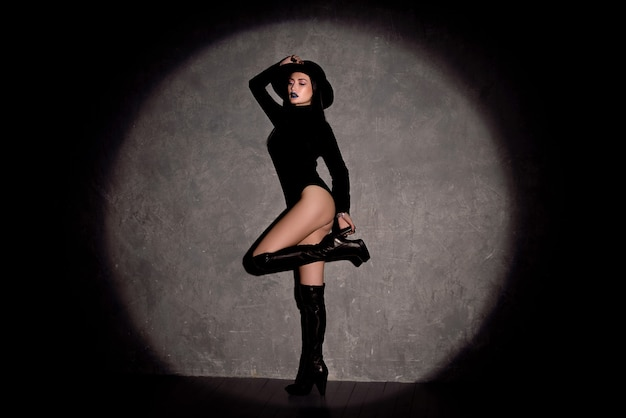 Hochmodeporträt der eleganten frau im schwarzen hut und im bodysuit. studioaufnahme.
