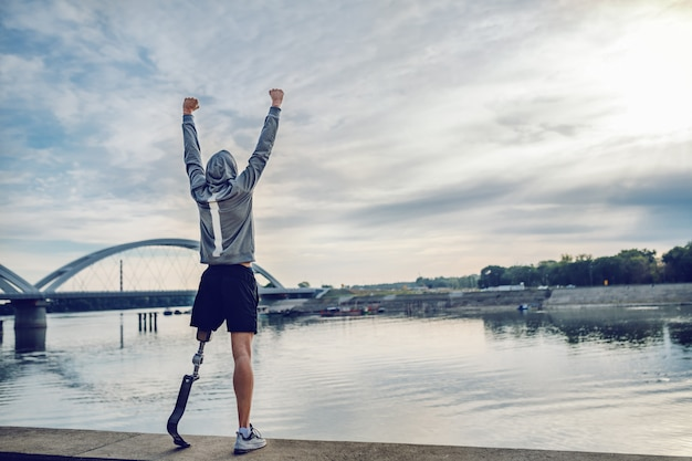 Hochmotivierter kaukasischer behinderter sportler in sportbekleidung und mit künstlichem bein, das auf dem kai steht und die arme hochhält.