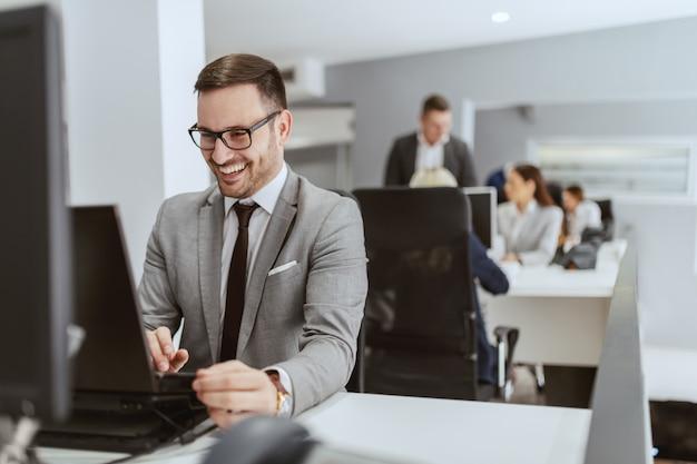 Hochmotivierter männlicher kaukasischer unrasierter lächelnder männlicher angestellter, der an seinem arbeitsplatz sitzt und computer benutzt.