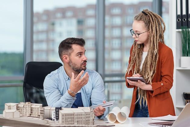 Hochqualifizierte, fleißige, kreative designerinnen und designer, die mit dem modell zukünftiger gebäude arbeiten