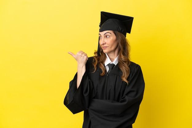 Hochschulabsolvent mittleren alters isoliert auf gelbem hintergrund, der auf die seite zeigt, um ein produkt zu präsentieren