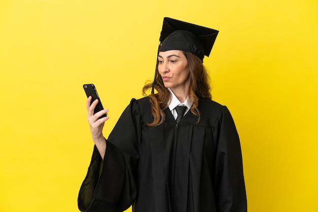 Hochschulabsolvent mittleren alters isoliert auf gelbem hintergrund, der ein selfie macht
