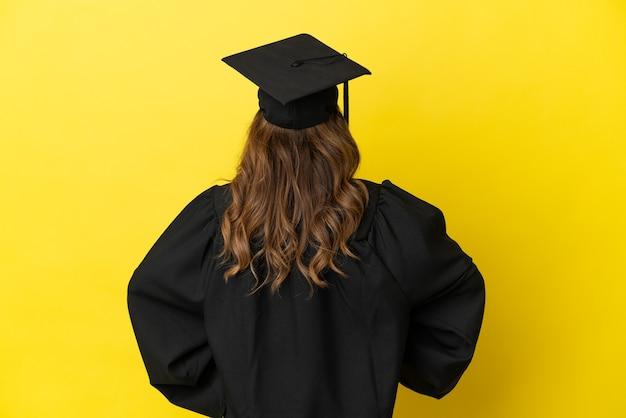Hochschulabsolvent mittleren alters isoliert auf gelbem hintergrund in der hinteren position