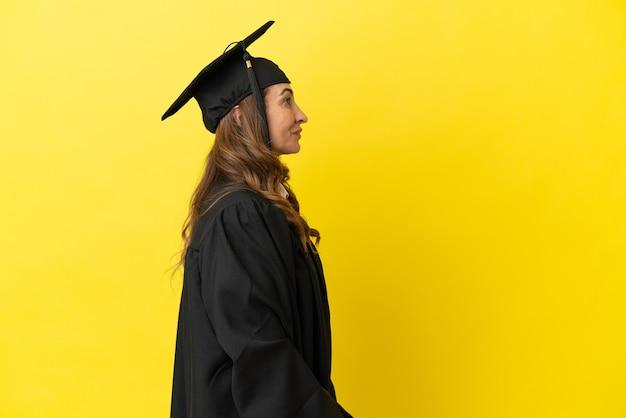 Hochschulabsolvent mittleren alters isoliert auf gelbem hintergrund lachend in seitenlage