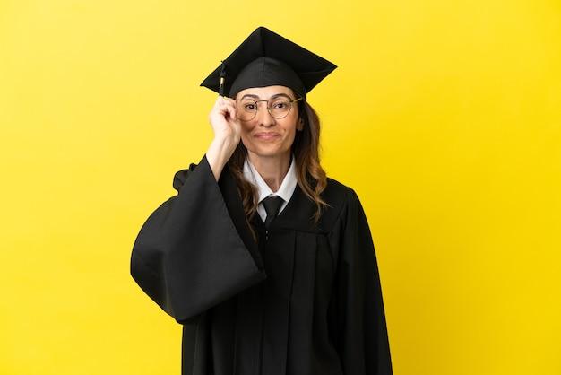 Hochschulabsolvent mittleren alters isoliert auf gelbem hintergrund mit brille und überrascht