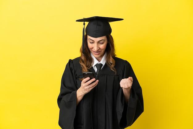 Hochschulabsolvent mittleren alters isoliert auf gelbem hintergrund überrascht und sendet eine nachricht