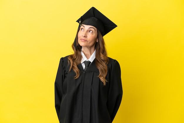 Hochschulabsolvent mittleren alters isoliert auf gelbem hintergrund und nach oben schauend