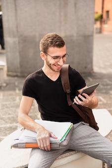 Hochschulstudent, der auf einer bank sitzt und an der tablette lächelt