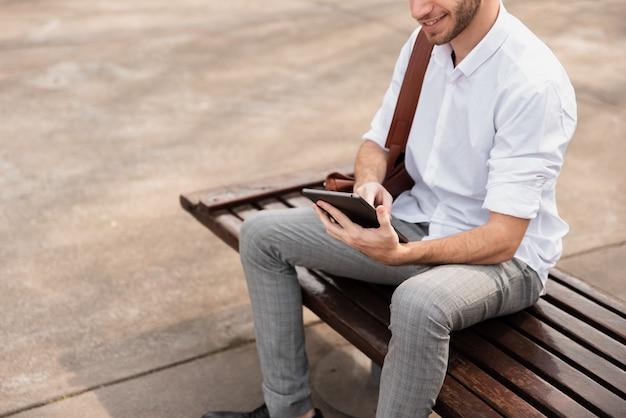 Hochschulstudent, der auf einer bank sitzt und die tablette verwendet