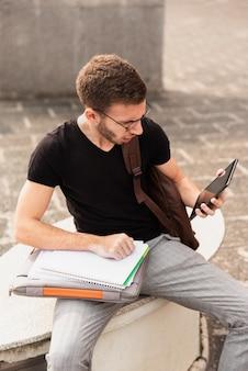 Hochschulstudent, der auf einer bank sitzt und tablette betrachtet