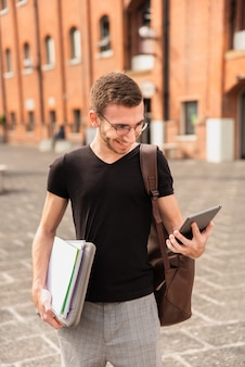 Hochschulstudent in der stadt, die seine tablette betrachtet
