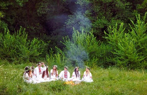 Hochsommer. junge leute in slawischer kleidung sitzen im wald in der nähe des feuers.