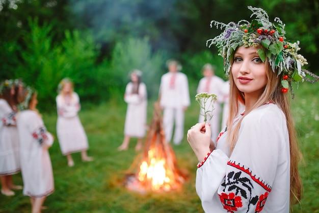 Hochsommer. porträt eines schönen mädchens in slawischer kleidung nahe dem feuer.