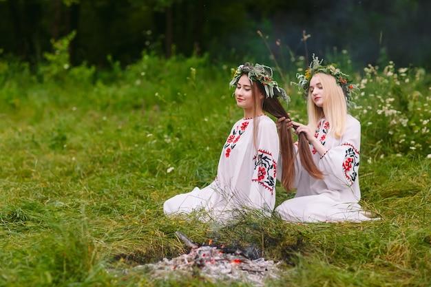Hochsommer. zwei mädchen in slawischer kleidung weben zöpfe in die haare in der nähe des feuers.