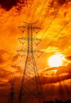 Hochspannungs-strommast und übertragungsleitungen. strommasten bei sonnenuntergang. kraft und energie. energieeinsparung. hochspannungsgitterturm mit kabel. goldener himmel.
