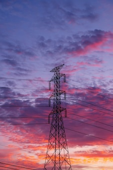Hochspannungs-strommaststange mit buntem sonnenuntergangshintergrund des himmels und der wolke Premium Fotos