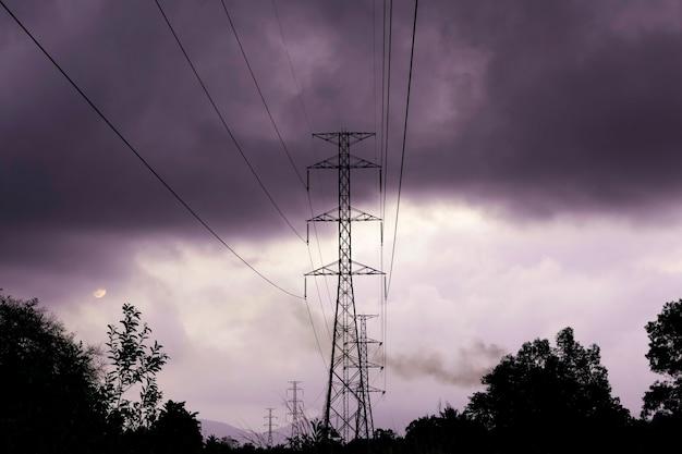 Hochspannungs-stromverteilungsmast mit baumschatten bei sonnenuntergang, strommast für die energieerzeugungsindustrie