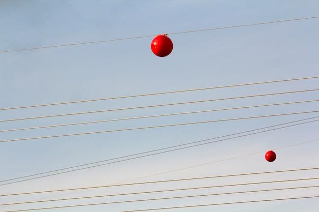 Hochspannungsleitung mit großem ball zur warnung von piloten, tiefflugzeugen und hubschraubern.