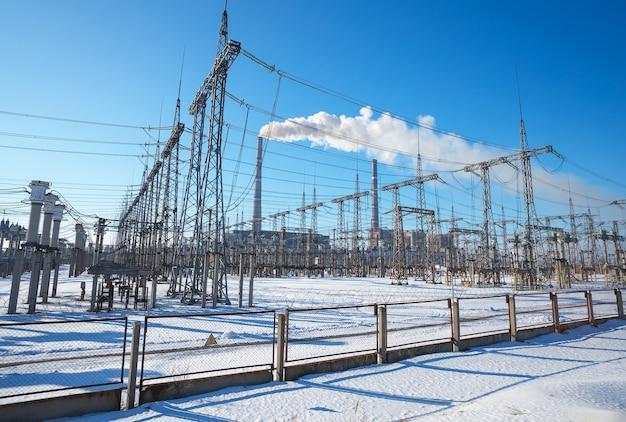 Hochspannungsleitungen im winter. wärmekraftwerk. hochspannungs-umspannwerk.