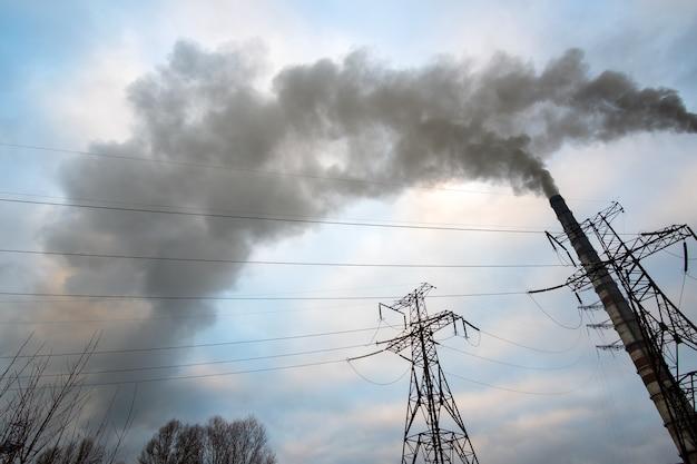Hochspannungsleitungen und kohlekraftwerksrohre mit aufsteigendem schwarzem rauch