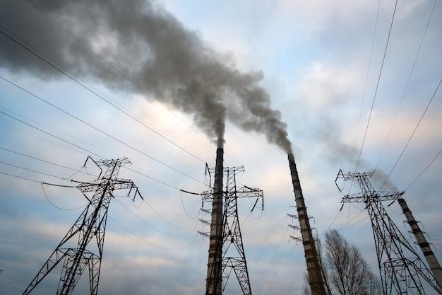 Hochspannungsleitungen und kohlekraftwerksrohre mit schwarzem rauch, der die umweltschädliche atmosphäre aufsteigt.