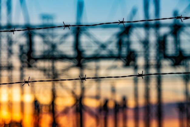 Hochspannungsleitungen von elektrischen verteilerstationen bei sonnenuntergang
