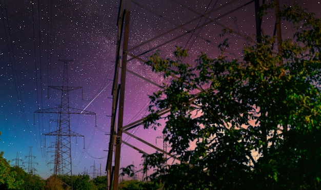 Hochspannungsmast mit milchstraße am himmel. industrielle ansicht von hochspannungsleitungen.