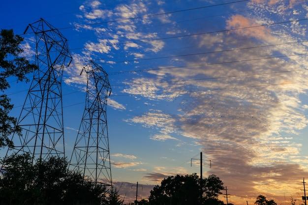 Hochspannungsmasten in der sonnenuntergangsszene sonnenuntergang himmelssonne stromkabel