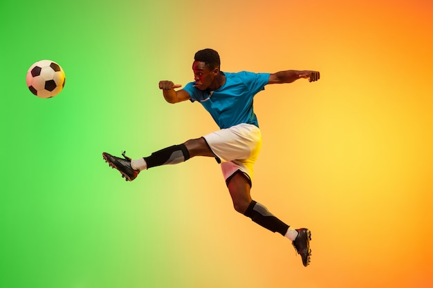 Hochspringen. männlicher fußball, fußballspielertraining in aktion einzeln auf gradientenstudiohintergrund im neonlicht. konzept der bewegung, aktion, erfolge, gesunder lebensstil. jugendkultur.