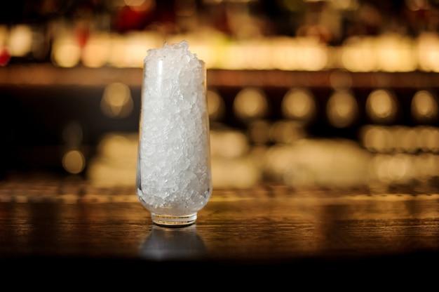 Hochtransparentes cocktailglas mit eiswürfeln auf der bartheke des pubs vor dem unscharfen hintergrund der lichter