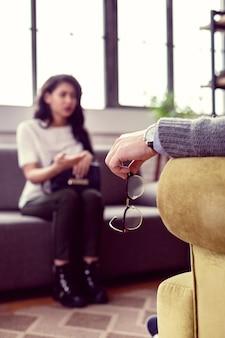 Hochwertige brillen. selektiver fokus einer männlichen hand, die während einer psychologischen sitzung die brille hält